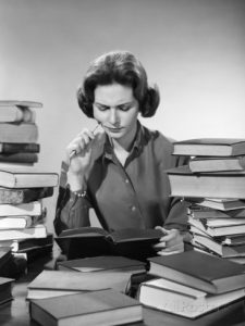 1950s-1960s-college-woman-studying-surrounded-all-around-by-piles-of-books